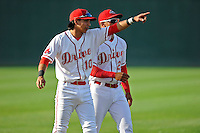 Shortstop Mauricio Dubon (10), left, and second baseman Yoan Moncada (24) of the Greenville Drive look into the stands before a game against the Lexington Legends on Tuesday, May 19, 2015, at Fluor Field at the West End in Greenville, South Carolina. The Cuban-born 19-year-old Red Sox signee has been ranked the No. 1 international prospect in baseball by Baseball America. (Tom Priddy/Four Seam Images)