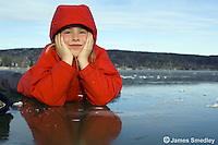 Happy young girl lying down on the ice of a frozen lake