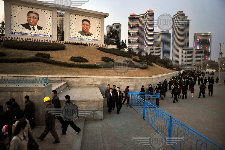 People leave a metro station (left) and pass some new paintings of Eternal President Kim Il-sung and Supreme Leader Kim Jong-il (right) created for the birthday celebrations for Kim Il-sung.......