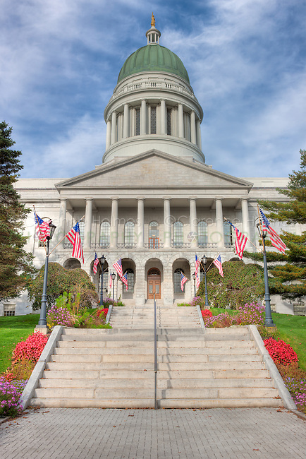 American flags flank the stairs to the front entrance of the Maine State House in Augusta, Maine.