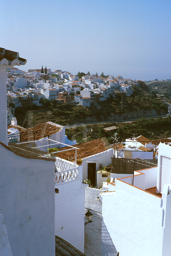 View towards the Mediterranean with red tile rooftops and white washed village in foreground. Frigiliana Andalucia Spain.