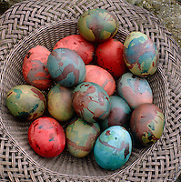 A festive multi-coloured pile of hand-painted eggs in a metal latticework basket