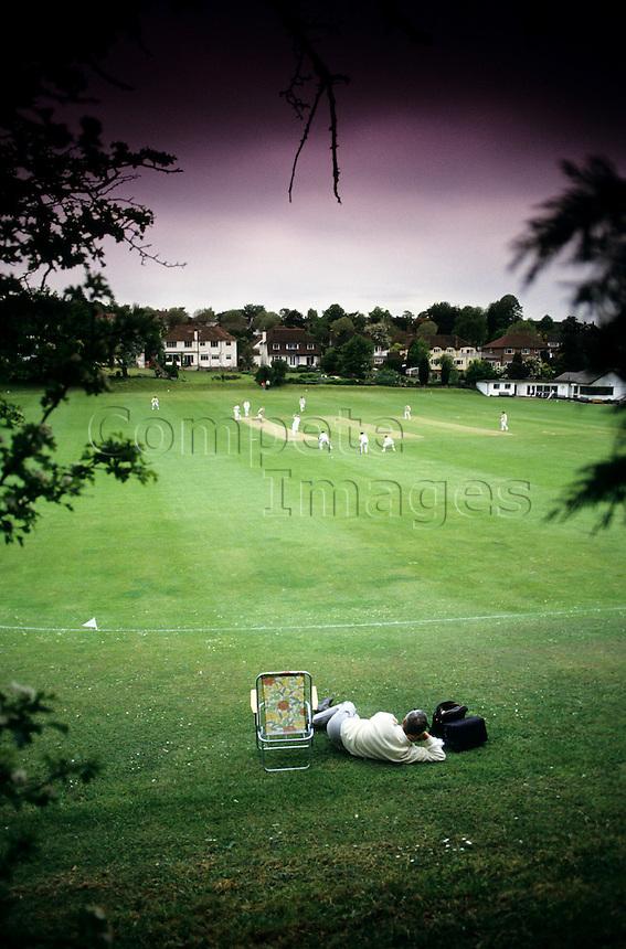 Spectator sitting under a tree watching a cricket match