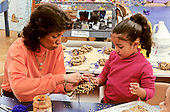 MR/ Schenectady, New York.Yates Arts-in-Education Magnet School / Pre-Kindergarten.Paraprofessional (African-American) helps girl (4, Puerto-Rican / Ecuadorian-American) make bird feeder of peanut butter and bird seed pine cone..MR:Cop2, Lup1       FC#:27373-00212.scan from slide.©Ellen B. Senisi