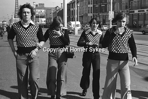 Two couples in matching V neck jumpers walking down the Golden Mile smoking cigarettes. Blackpool promenade, Lancashire England 1974