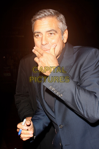 George Clooney.'The Ides Of March' UK premiere, London Film Festival, Odeon Leicester Square cinema, Leicester Square, London, England..19th October 2011.LFF half length blue suit jacket black shirt mouth hand covering funny pen .CAP/AH.©Adam Houghton/Capital Pictures.