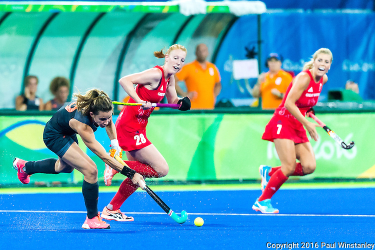 Carlien Dirkse van den Heuvel #9 of Netherlands passes watched by Nicola White #28 of Great Britain and Georgie Twigg #7 of Great Britain during Netherlands vs Great Britain in the gold medal final at the Rio 2016 Olympics at the Olympic Hockey Centre in Rio de Janeiro, Brazil.