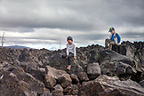 USA, Oregon, Oregon Cascades, two boys play around on the rocks at the Dee Wright Observatory in the middle of an old lava flow at the top of the McKenzie Pass on Hwy 242, the Wilamette National Forest