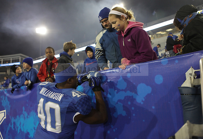 UK linebacker Avery Williamson (40) signs autographs for fans after the University of Kentucky Homecoming football game against Alabama State at Commonwealth Stadium in Lexington, Ky., on Saturday, November 2, 2013. Photo by Emily Wuetcher | Staff