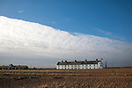 Frontal clouds passing over Coastguard Cottages shingle beach at Shingle Street, Suffolk, England, UK