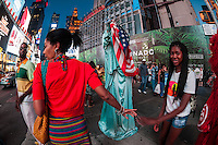 New York, NY - 11 July 2014 Person in a Statue of Liberty costom sheilds their face from the camera with an American Flag ©Stacy Walsh Rosenstock/Alamy