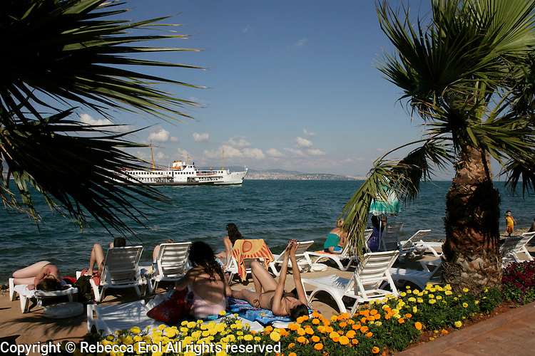 On the beach at Kinaliada as a ferry passes, Istanbul, Turkey