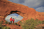Couple visiting Double Arch at sunset in Arches National Park, Utah, USA. .  John offers private photo tours in Arches National Park and throughout Utah and Colorado. Year-round.