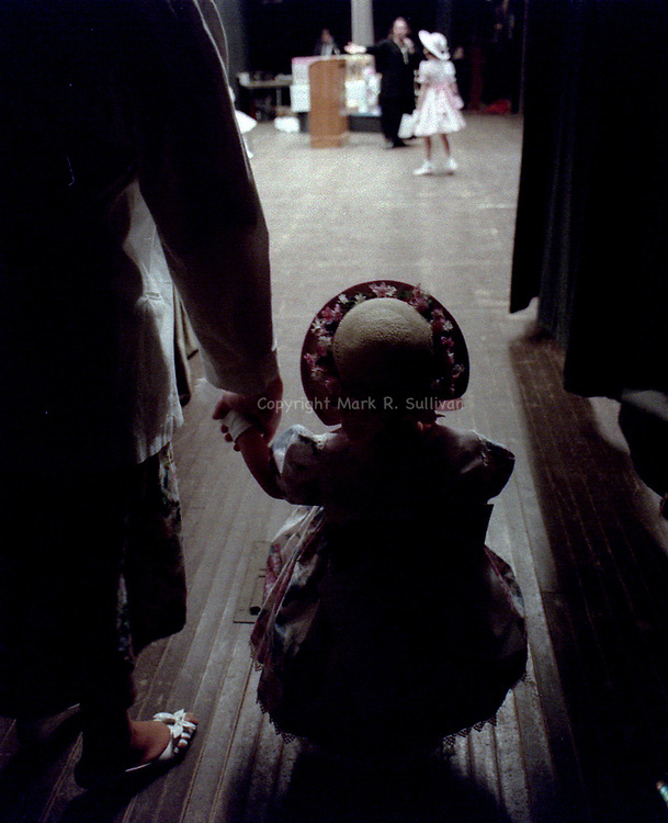 Nina Marqurum holds her mother's hand before heading to the stage for Asbury park's annual Easter parade.