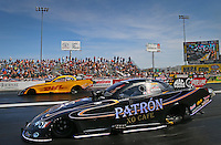 Mar 28, 2014; Las Vegas, NV, USA; NHRA funny car driver Alexis DeJoria (near) races alongside teammate Del Worsham during qualifying for the Summitracing.com Nationals at The Strip at Las Vegas Motor Speedway. Mandatory Credit: Mark J. Rebilas-USA TODAY Sports