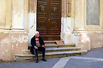 A Maltese man sits on the steps of one of the 359 churches in Malta, in the city of Valetta.