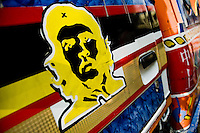 The Che Guevara's famous portrait painted on the body of a tap-tap bus operating in Port-au-Prince, Haiti, 25 July 2008. Tap-tap vehicles serve as public transportation in Haiti. They are private, operate over fixed routes, departing only when full. Tap-taps are decorated with bright and shiny colors and with a lot of fancy designed elements. There are scenes from the Bible, Christian slogans, TV stars or famous football players often painted on a tap-tap body. Tap-tap name comes from sound of taps on the metal bus body signifying a passenger's request to be dropped off.
