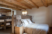 The bedroom is designed with contemporary rusticity with double wash basins concealed behind the massive wooden headbaord