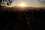 People observe the sun setting near the top of Mount Fuji atop Mount Takao in Tokyo December 26, 2015. (Photo by Yuriko Nakao/AFLO)