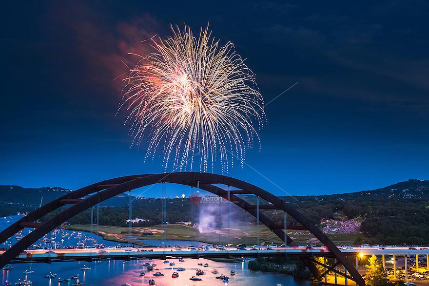 Fireworks light the night sky over the 360 Bridge on Lake Austin, TX.