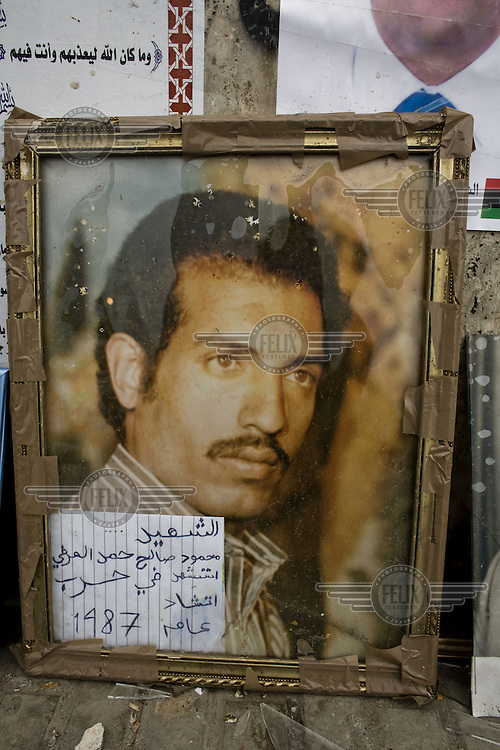A framed photograph of a missing man with a note written in Arabic placed outside the central courthouse in Benghazi. The courthouse has become a focal point for relatives of people who have gone missing in Libya in recent years and during the 2011 civil war. Many relatives bring photographs of their missing family members and leave them outside the courthouse. ..