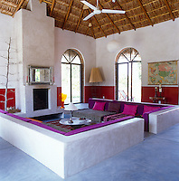 A side view of the large concrete seating area in the living room which is softened by throws, cushions and covers in vibrant pinks and purples