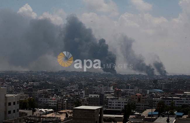 Smoke rises after an Israeli missile hit Shajaiyeh neighborhood in Gaza City, northern Gaza Strip, Sunday, July 20, 2014. Hundreds of panicked residents have fled the neighborhood which they say has come under heavy tank fire from Israeli forces. Some reported seeing dead and wounded in the streets, with ambulances unable to reach the area. Israel widened its ground offensive early Sunday, sending more troops into the Hamas-ruled territory to destroy tunnels used by the Islamic militants to try to sneak into Israel.  Photo by Ashraf Amra