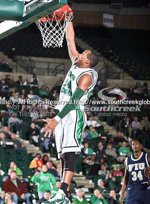 North Texas Mean Green forward Kedrick Hogans (24) gets a slam dunk in the NCAA  basketball game between the Florida International University Panthers and the University of North Texas Mean Green at the North Texas Coliseum,the Super Pit, in Denton, Texas. UNT defeated FIU 87 to 77