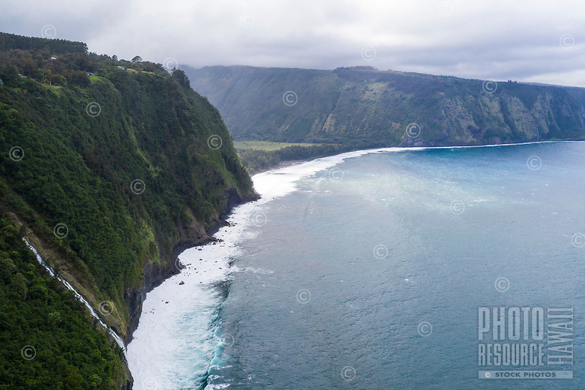 An aerial view of a waterfall and Waipi'o Valley, Big Island of Hawai'i.