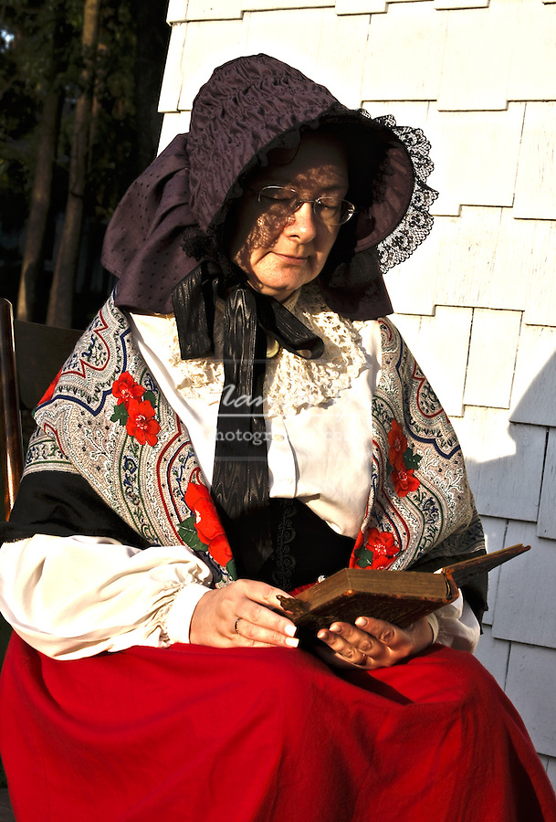 A lady wearing a bonnet reading a book outside