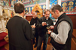 Fathers Blasko Paraklis and Budimir Andjelic converse as Dan Stojanovich fills a censer held by Miloje Milinkovic inside St. Sava Church, Jackson.
