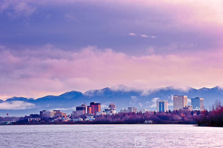 Photo of the Anchorage City Skyline located on the shores of Knik arm before sunrise, high tide, taken from the Tony Knowles Coastal Trail, fall, Southcentral Alaska, USA.