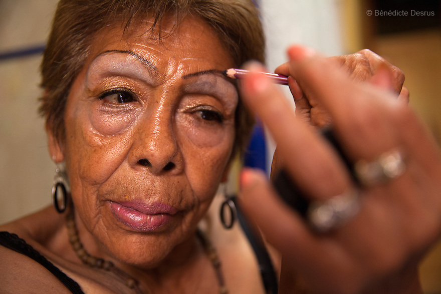 Luchita, a resident of Casa Xochiquetzal, puts on makeup in her bedroom at the shelter in Mexico City, Mexico on May 25, 2016. Casa Xochiquetzal is a shelter for elderly sex workers in Mexico City. It gives the women refuge, food, health services, a space to learn about their human rights and courses to help them rediscover their self-confidence and deal with traumatic aspects of their lives. Casa Xochiquetzal provides a space to age with dignity for a group of vulnerable women who are often invisible to society at large. It is the only such shelter existing in Latin America. Photo by Bénédicte Desrus