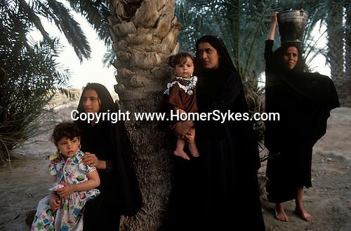 Marsh Arabs. Southern Iraq. Circa 1985. Marsh Arab women and children collecting water banks of river Tigris.