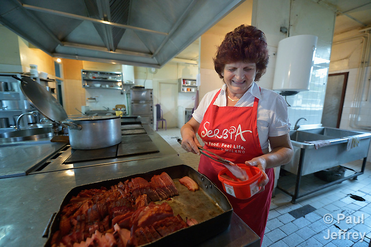 A woman prepares food at the Krnjaca Center for Refugees on the outskirts of Belgrade, Serbia.
