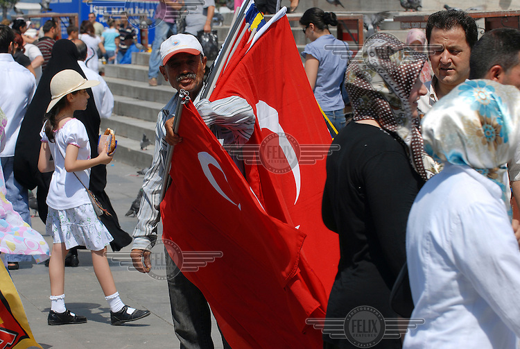 Crowds move around a flag seller in the Eminonu District of Istanbul.