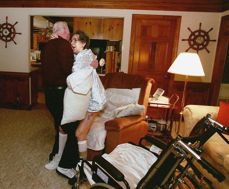 "4/4/00.THOMASON HOME -- Retired Army Col. Dana ""Tommy"" Thomason lifts his wife Barbara from her wheelchair to a recliner as she screams in pain. Tommy is the only care-giver for his wife after a stroke paralyzed her. The Thomason's lost military health care at the age of 65 and Medicare does not cover her home health care..CONGRESSIONAL QUARTERLY PHOTO BY DOUGLAS GRAHAM"