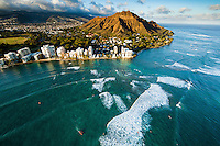 At sunset, waves rush towards the beach along the Gold Coast of O'ahu, with Diamond Head in the distance.