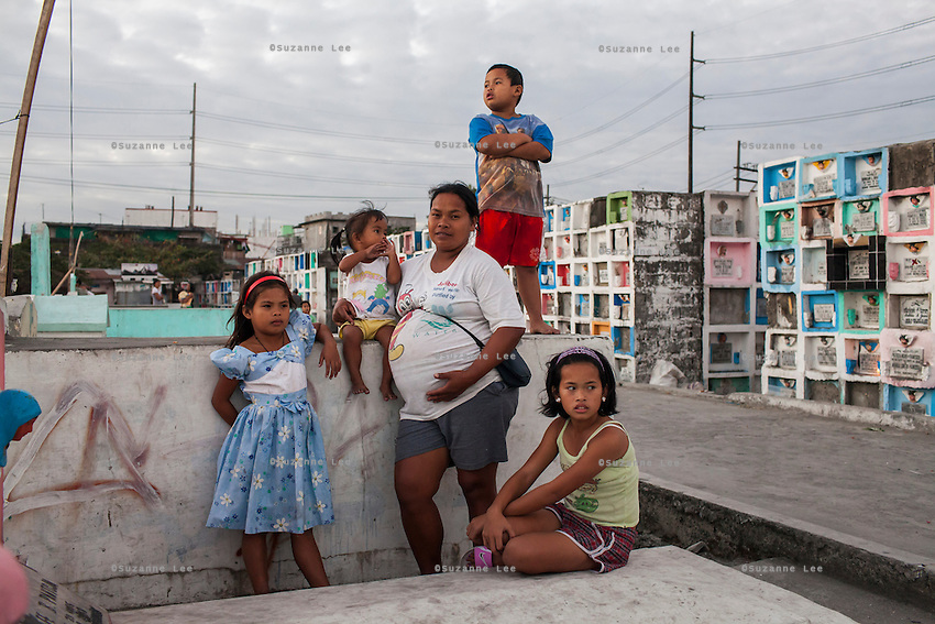 (L-R) Christine Joy, 9, Carla Mae, 2, Rose Marie Ferrer, 33, John Key, 7, and Charlene, 11, pose for a family portrait in an inhabited cemetery where they live in Paranaque City, Metro Manila, The Philippines on 18 January 2013. Rose owns a shop in the cemetery where she sells funeral items. She supports her family with this, has breastfed all her 5 children, and is 9 months pregnant now. Photo by Suzanne Lee for Save the Children UK