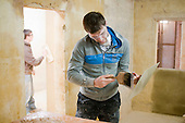 Plastering student uses a brush to make sure the hawk is wet, Able Skills, Dartford, Kent.
