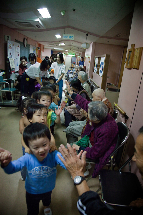Tokyo - 3rd of December 2009 - Kotohen nursery and nursing home in the Edogawa district. Elderly and children clap their hands after the visit of the kids.