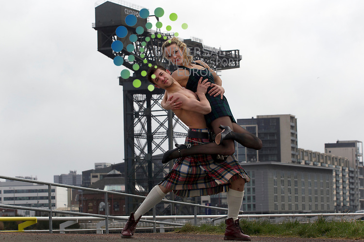 """Scottish ballet dancers Remi Andreoni (Left) with Sophie Laplane (right) dressed in tartan near the river clyde with the Clydeport crane to help launch the Matthew Bourne's forthcoming production """"Highland Fling"""" ..Picture: Universal News And Sport (Europe) 19 March 2013.."""