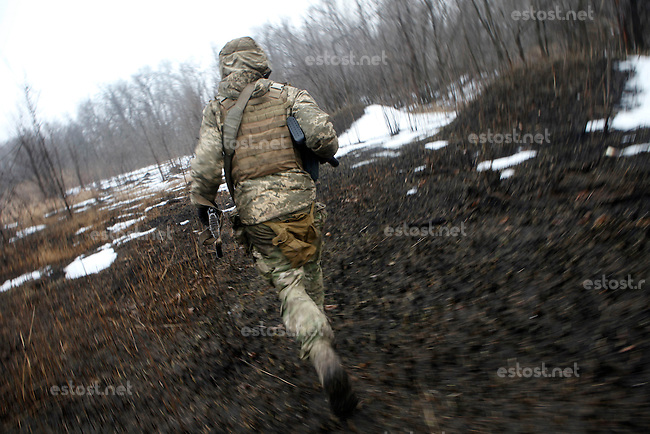 "UKRAINE, 02.2016, Oblast Donetsk. Ukrainian-Russian conflict concerning Eastern Ukraine / Foreign volunteers (""Task Force Pluto"") fighting with the far-right militia Pravyi Sektor against the Russian-backed separatists: Charlie (USA) runs under enemy fire across a muddy field on an ammunition re-supply mission. © Timo Vogt/EST&OST"