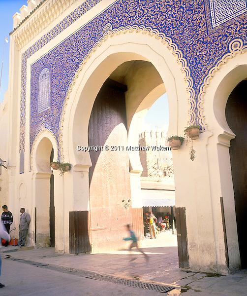 FES, MOROCCO: A young Moroccan boy runs through the an arch of the Bab Bou Jeloude entrance to the medina in Fez. Fes al Bali, Morocco.