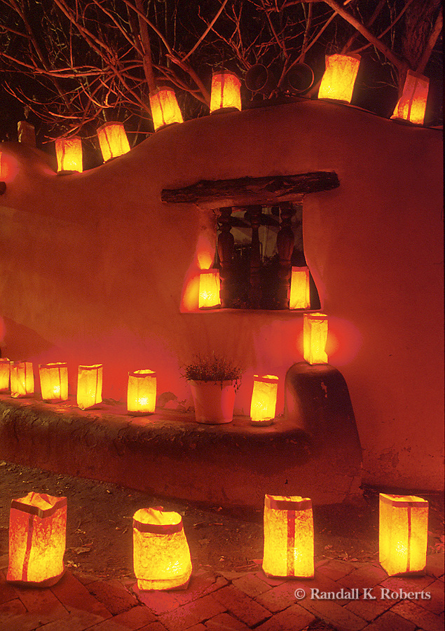 Christmas eve luminarias light an adobe wall in Old Town Albuquerque, New Mexico