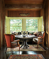 A games table and a cosy seating area fill a bay window in the wood-lined living room with views over the lake