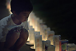 A boy inspects candles lining a path in Nagasaki, Japan, on August 8, 2015, the eve of the 70th anniversary of the U.S. bombing of the port city with an atomic bomb. The candles represent a memorial to those who died and a prayer for peace, including an end to nuclear weapons.