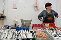 Female stallholder, marketing her fishy wares, in the daily fishmarket, Zadar, Croatia.