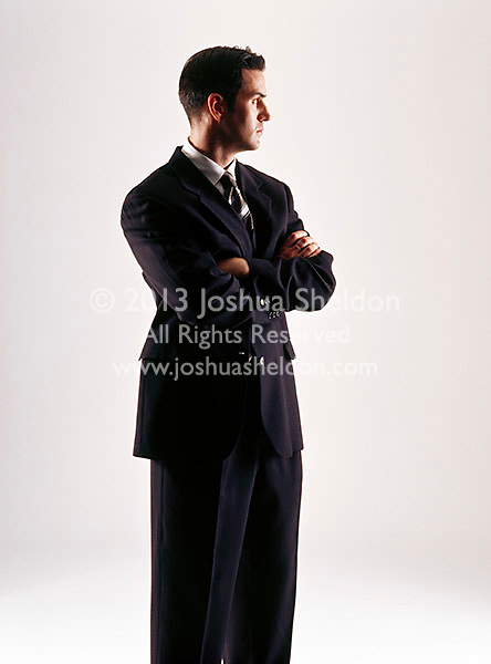 Caucasian looking man wearing a dark business suit looking sideways with arms folded over his chest