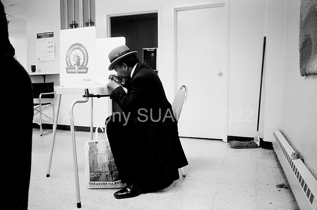 Chicago, Illinois.November 4, 2008.USA..On election day in the United States residents of Chicago's South-side vote early. A man uses a magnifying glass to read his ballot.